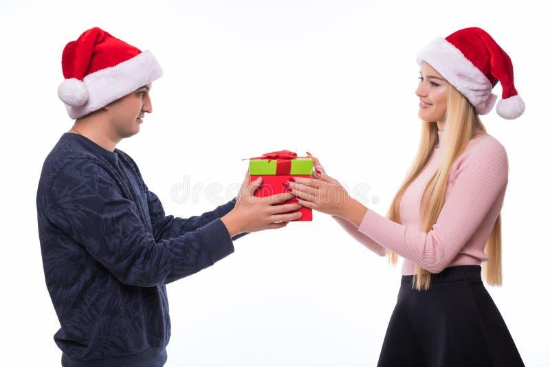 Equipe a doação da caixa de presente do Natal à mulher isoloated no fundo branco, par no chapéu de Santa fotos de stock