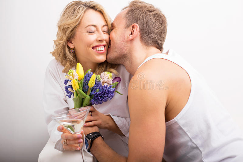 Equipe a doação de flores e o beijo da amiga em seu mordente imagem de stock royalty free