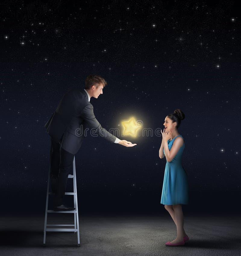 Equipe a doação de uma estrela do céu a uma mulher imagens de stock