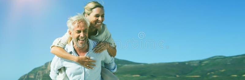 Equipe a doação sua esposa de riso de um reboque na praia fotografia de stock