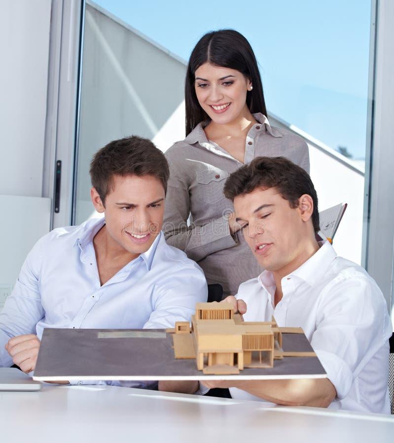 Equipe dos arquitetos com modelo da casa foto de stock royalty free