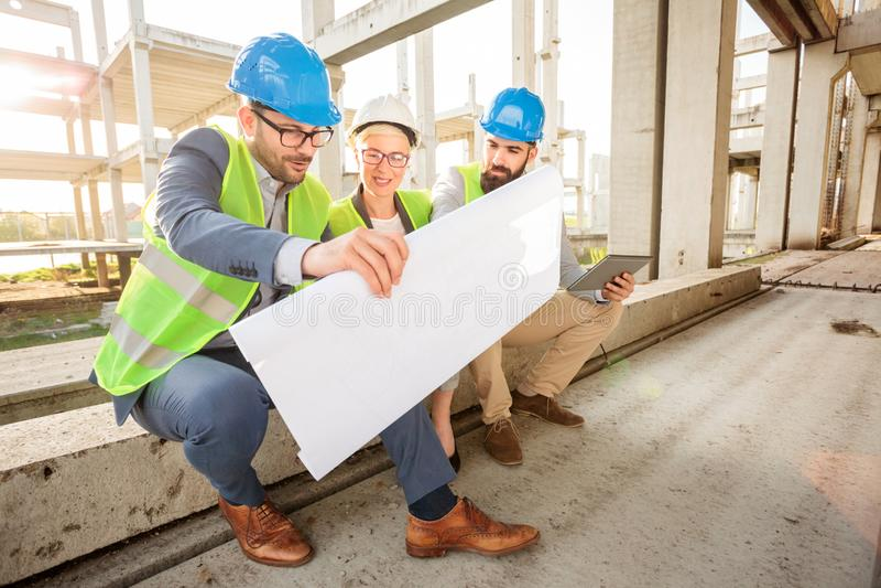 Equipe dos arquitetos novos bem sucedidos que olham plantas baixas durante uma reunião imagem de stock royalty free