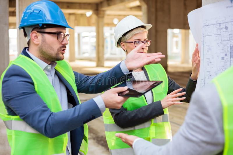 Equipe dos arquitetos novos que discutem e que discutem durante uma reunião sobre um canteiro de obras imagens de stock royalty free