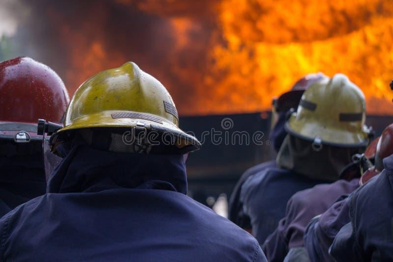 A equipe dos bombeiros foi treinada a extinguir a chama enorme fotos de stock