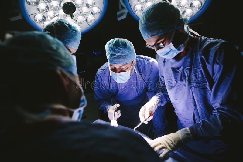 Equipe dos cirurgiões profissionais que executam a cirurgia imagens de stock