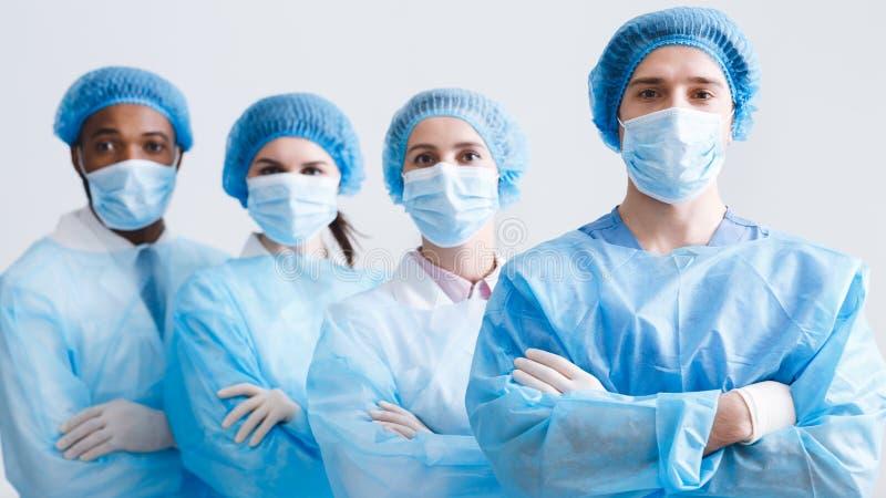 Equipe dos cirurgi?es Os doutores Wearing Protetor Uniforme, olham a câmera fotos de stock