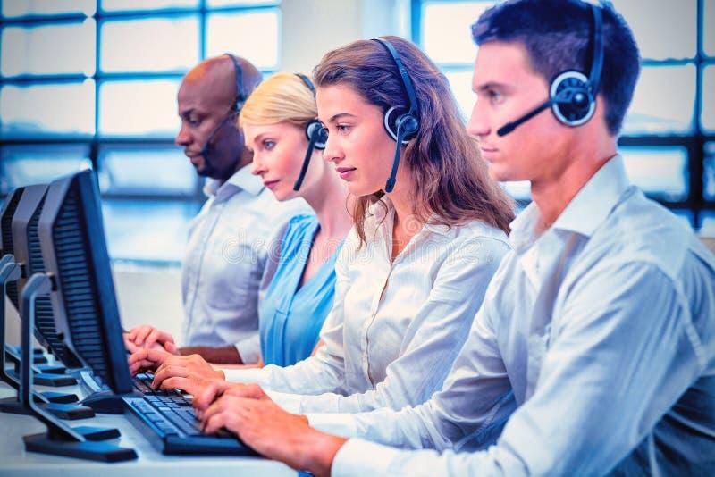 Equipe dos colegas que trabalham no computador com auriculares fotos de stock royalty free