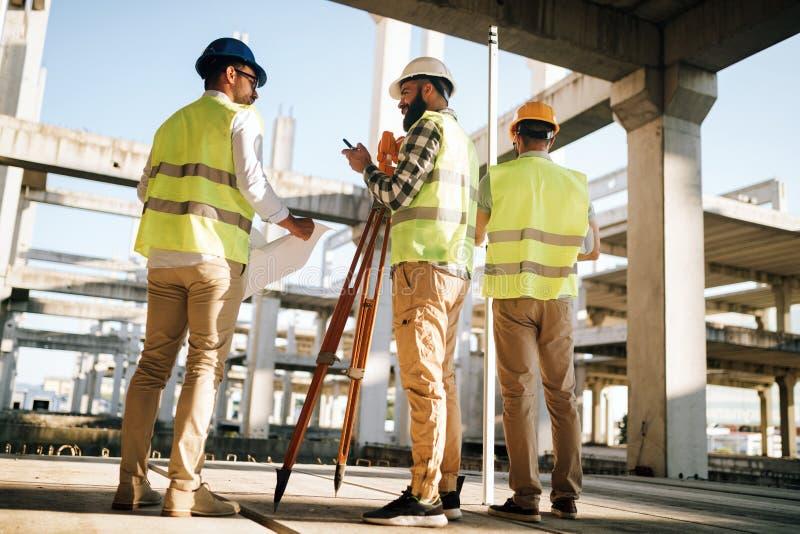 Equipe dos coordenadores de construção que trabalham no terreno de construção foto de stock