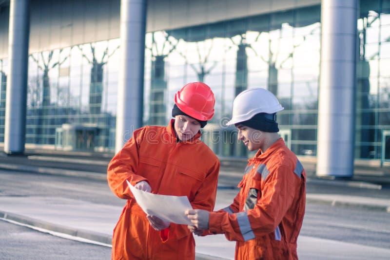 Equipe dos coordenadores novos que discutem um projeto de construção fotos de stock