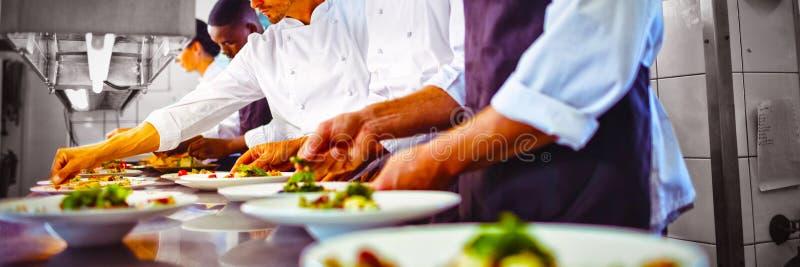 Equipe dos cozinheiros chefe que decoram a refeição no contador imagem de stock