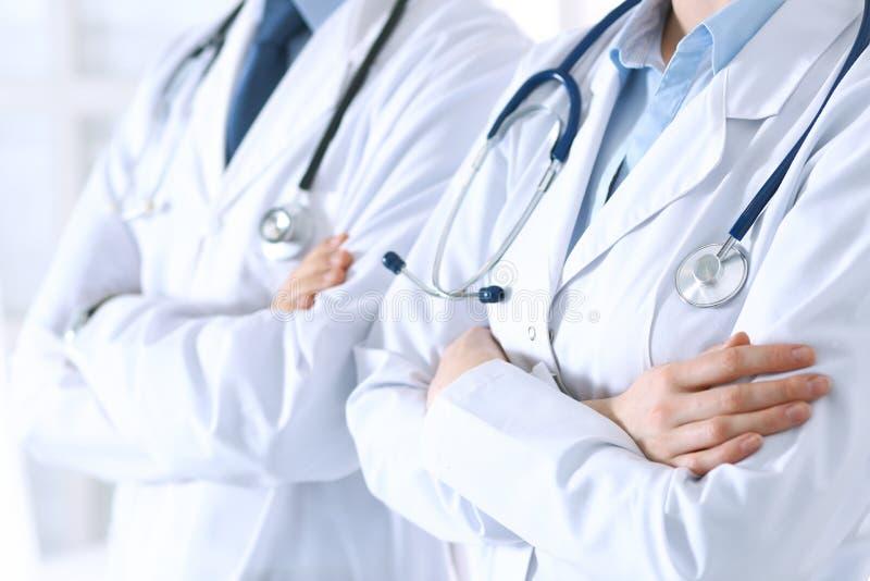 A equipe dos doutores desconhecidos que estão em linha reta com braços cruzou-se no hospital Médicos prontos para ajudar Cuidados imagens de stock