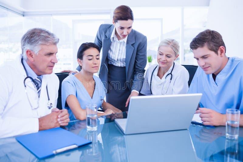 Equipe dos doutores e da mulher de negócios que têm uma reunião fotos de stock royalty free