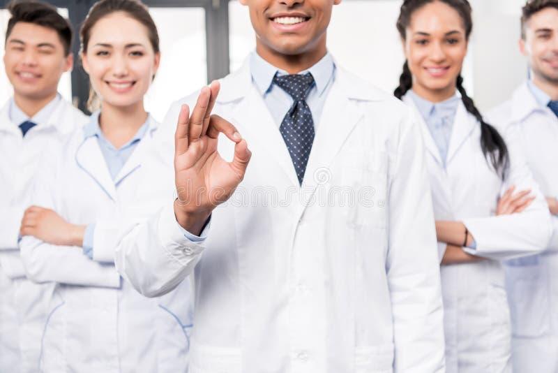 Equipe dos doutores profissionais de sorriso que estão junto quando seu líder mostrar está bem imagens de stock royalty free