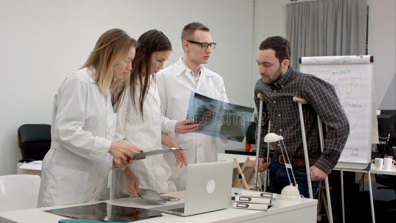A equipe dos doutores que explicam o raio X resulta ao paciente masculino em muletas imagem de stock royalty free