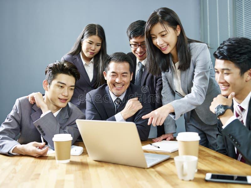 Equipe dos executivos asiáticos que trabalham junto no escritório imagens de stock