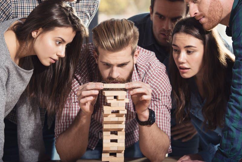 A equipe dos executivos constrói uma construção de madeira conceito da partida dos trabalhos de equipa, da parceria e da empresa fotos de stock royalty free