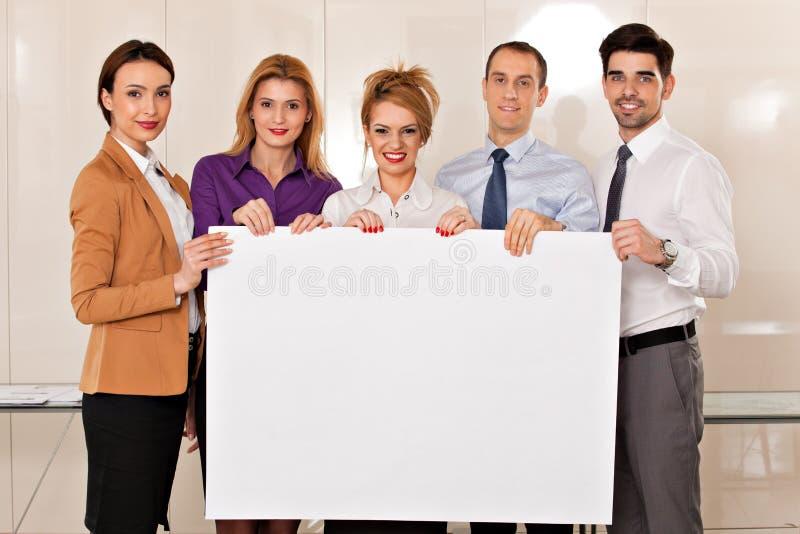 Equipe dos executivos que guardam o cartão imagem de stock