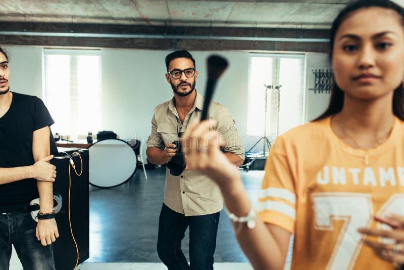 Equipe dos fotógrafo em um estúdio durante uma sessão fotográfica imagem de stock royalty free