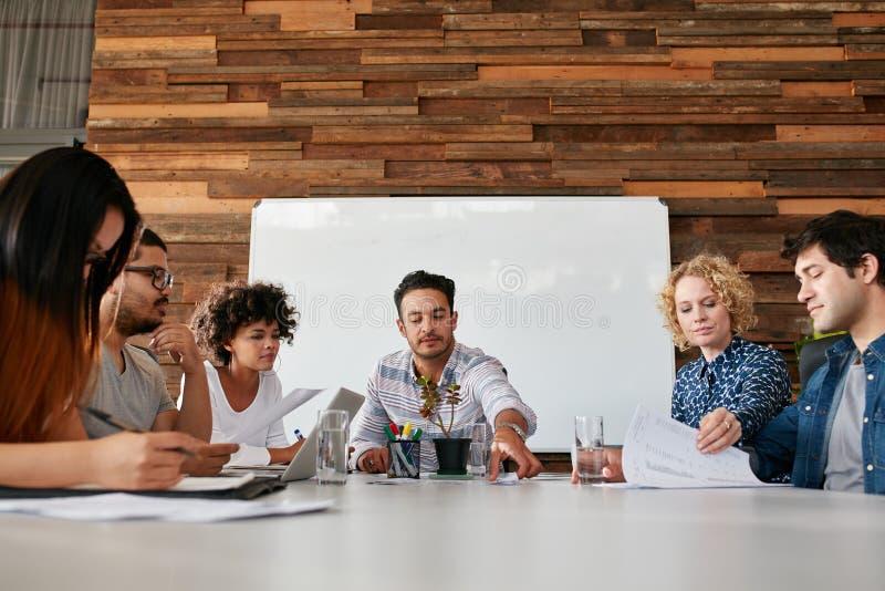 Equipe dos jovens que têm uma reunião no escritório fotografia de stock royalty free