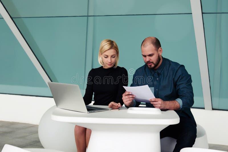 Equipe dos líderes especializados que usam o laptop e dos originais de papel para desenvolver um projeto novo fotos de stock royalty free