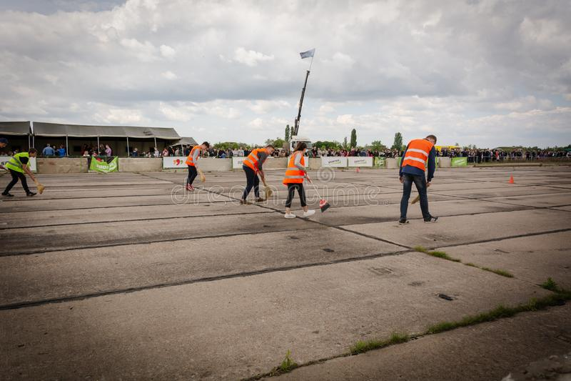 A equipe dos líquidos de limpeza em revestimentos alaranjados limpa a pista em carros de competência do arrasto em Transnistria imagens de stock royalty free