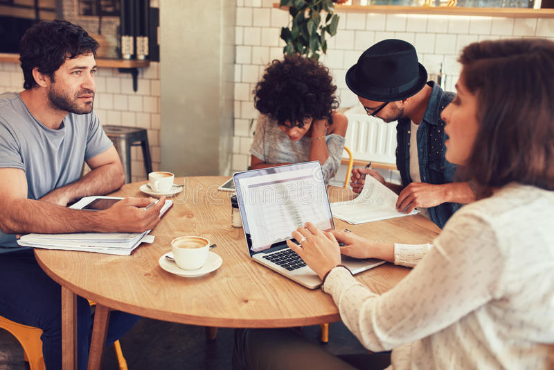 Equipe dos povos criativos que encontram-se em um café imagens de stock royalty free