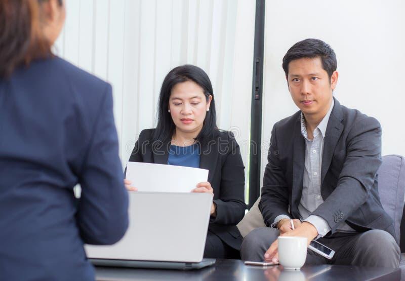 Equipe dos povos do negócio três que trabalham junto em um portátil com durante uma reunião que senta-se em torno de uma tabela imagens de stock royalty free