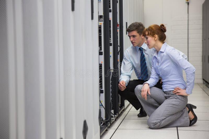 Equipe dos técnicos que ajoelham-se e que olham servidores imagens de stock