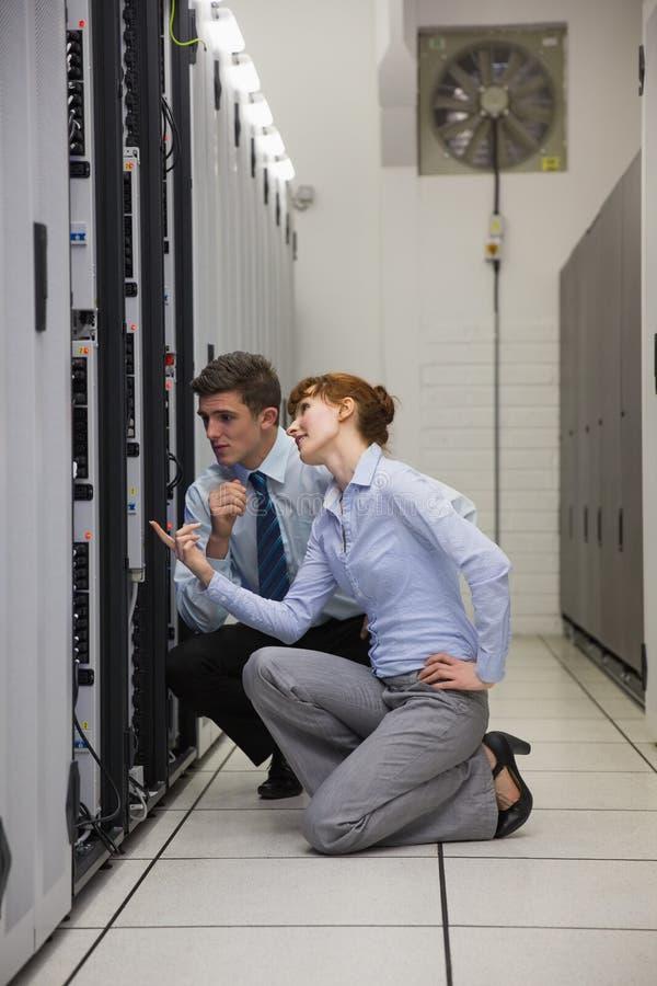 Equipe dos técnicos que ajoelham-se e que olham servidores fotos de stock royalty free