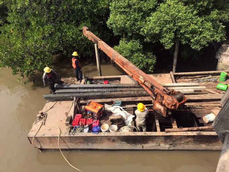 A equipe dos trabalhadores puxa as colunas concretas fora da água fotografia de stock