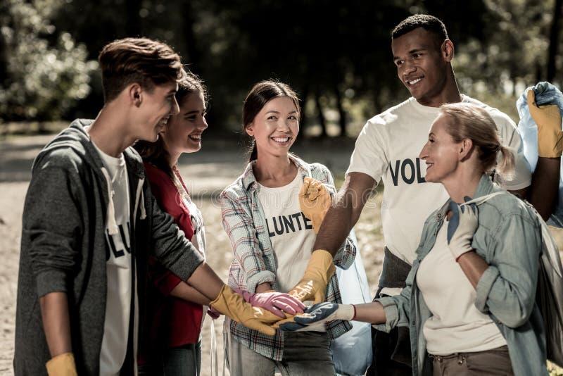 Equipe dos voluntários diligentes que apreciam sua empresa que trabalha extremamente junto imagem de stock royalty free