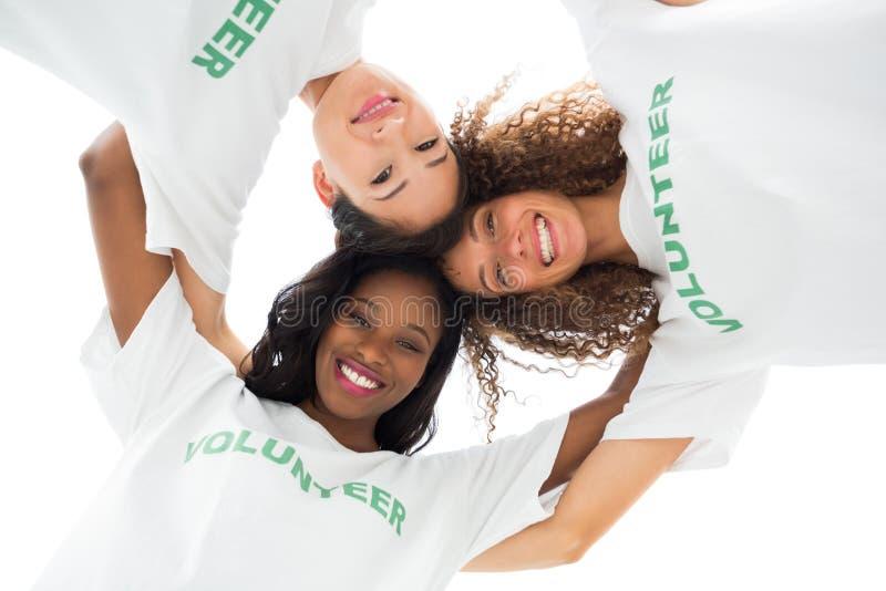 Equipe dos voluntários felizes que abraçam e que olham para baixo na câmera imagem de stock royalty free