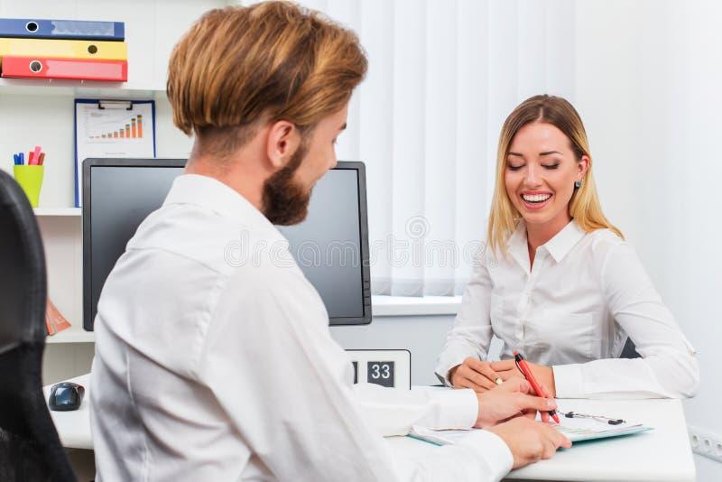 Equipe e uma mulher que está sendo entrevistada no escritório imagens de stock