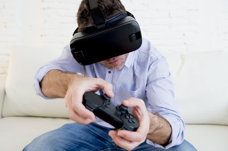Equipe em casa o jogo de utilização entusiasmado dos óculos de proteção 3d do sofá do sofá da sala de visitas imagens de stock