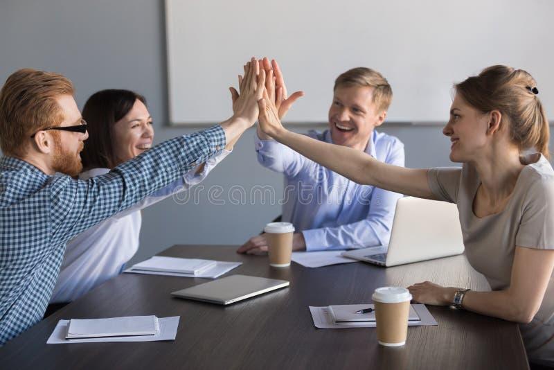 Equipe entusiasmado do negócio dos empregados que dão a elevação cinco durante o meeti foto de stock royalty free