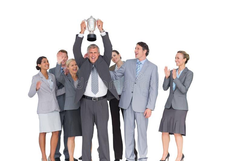 Equipe entusiasmado do negócio que cheering na câmera com troféu imagens de stock royalty free