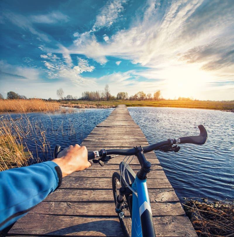 Equipe a equitação em uma bicicleta através da ponte foto de stock