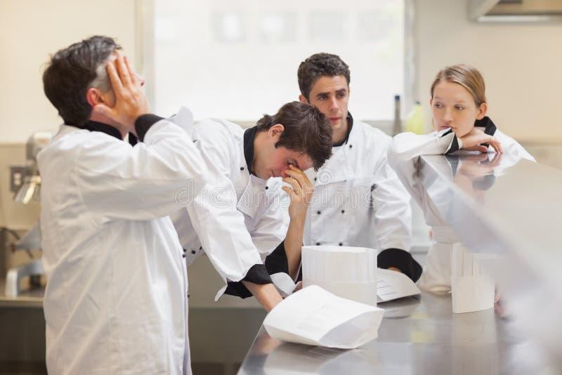 Equipe esgotada dos cozinheiros chefe fotos de stock