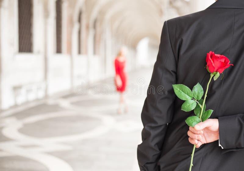 Equipe a espera de sua data com a rosa do vermelho atrás do seu para trás fotos de stock royalty free