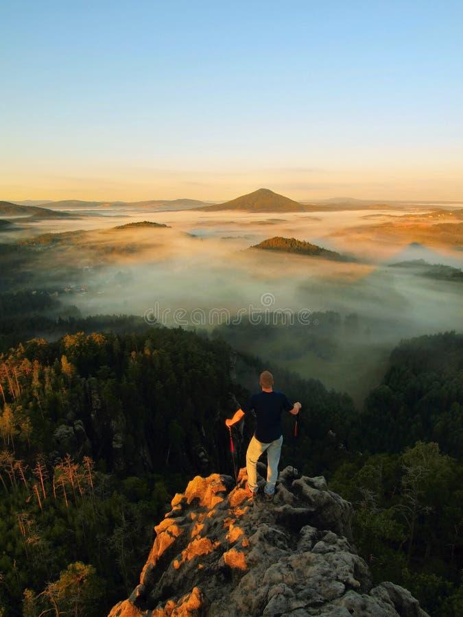 Equipe a estada no pico rochoso e dentro do relógio da aurora sobre o vale enevoado e nevoento da manhã Manhã bonita do outono fotografia de stock