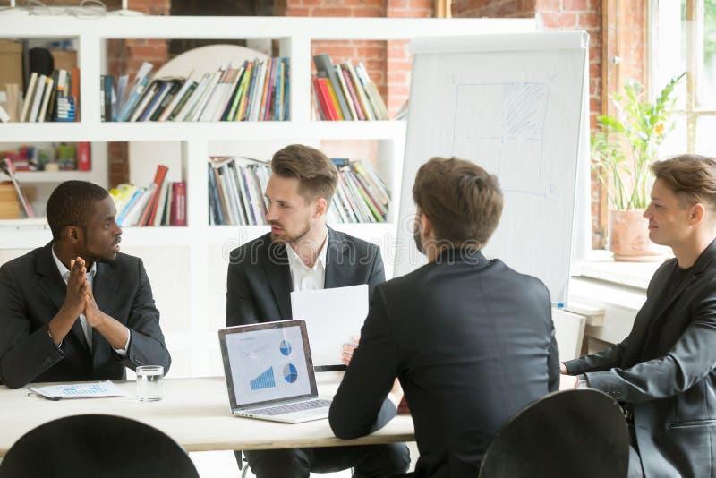 A equipe executiva diversa do negócio que discute o trabalho resulta no corpo fotos de stock royalty free