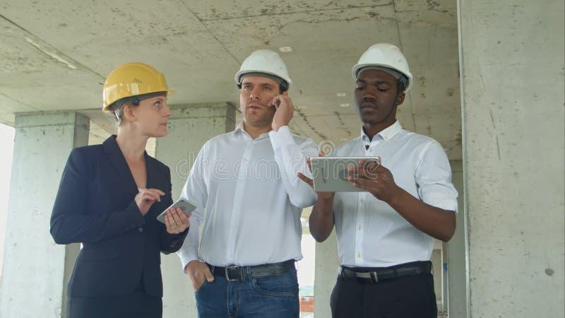 Equipe executiva no canteiro de obras que revê com tabuleta, smartphone, pessoa vestido formal que lê a tabuleta da construção fotos de stock royalty free