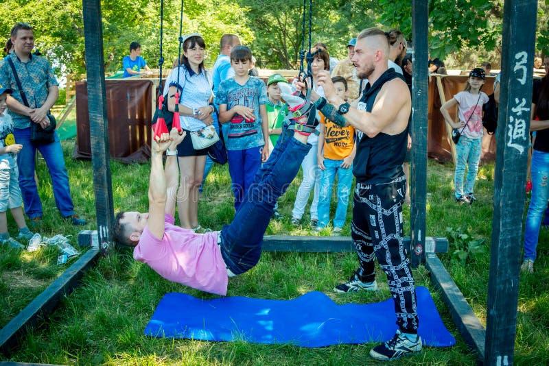 Equipe exercícios de tentativa da gravidade do alfa no festival da caridade da família em um parque da cidade imagens de stock royalty free