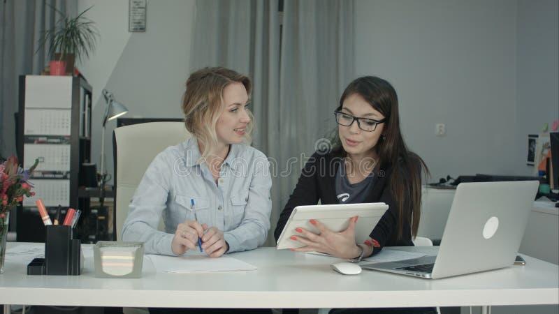 Equipe fêmea de sorriso do negócio que trabalha com o PC da tabuleta no escritório fotografia de stock royalty free