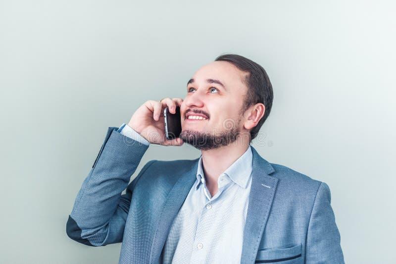 Equipe a fala no telefone, olhe acima e sorria Homem de negócios feliz sobre a boa notícia imagem de stock royalty free