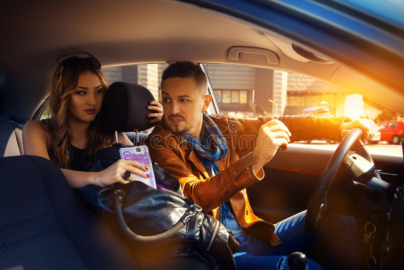 Equipe a fala a uma jovem mulher em um carro com um saco completo do dinheiro E imagem de stock