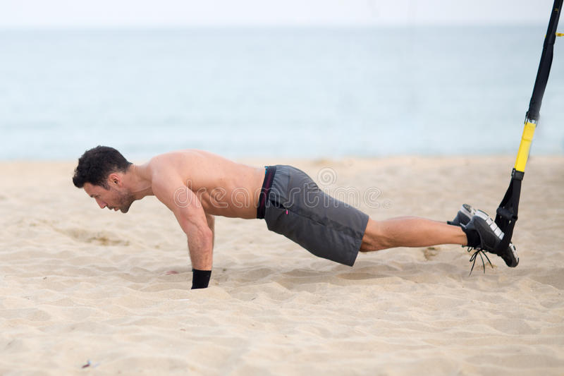 Equipe a fatura do exercício do trx do pé na praia foto de stock