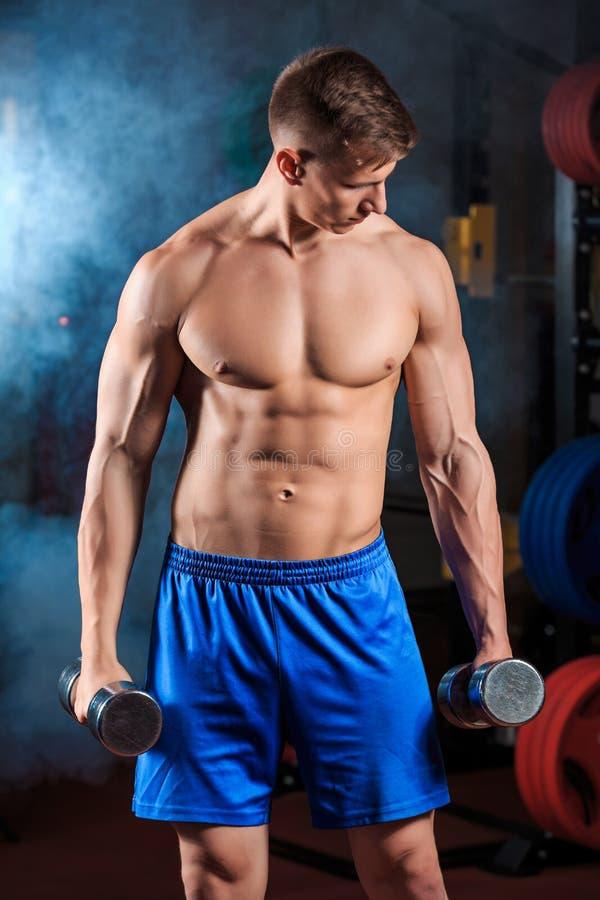 Equipe fazer o exercício pesado com pesos no gym imagem de stock