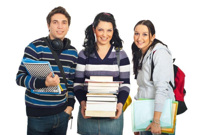 Equipe feliz de três estudantes imagens de stock