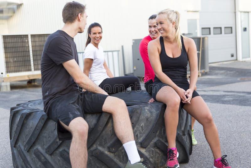Equipe feliz do exercício que senta-se em um pneu e que toma uma ruptura exterior imagens de stock